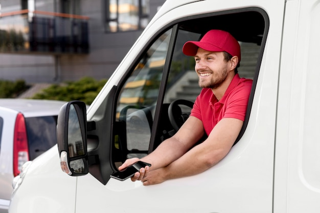 Delivery man in car with mobile