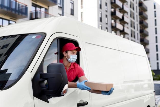 Uomo di consegna in auto con pacchetto