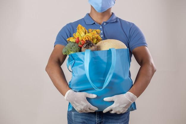 フェイスマスクと手袋と果物と野菜の袋を運ぶ配達人