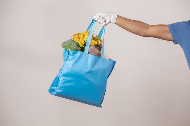 果物と野菜の袋を運ぶ配達人