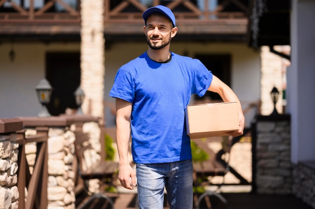 Delivery man carrying cardboard box outdoors