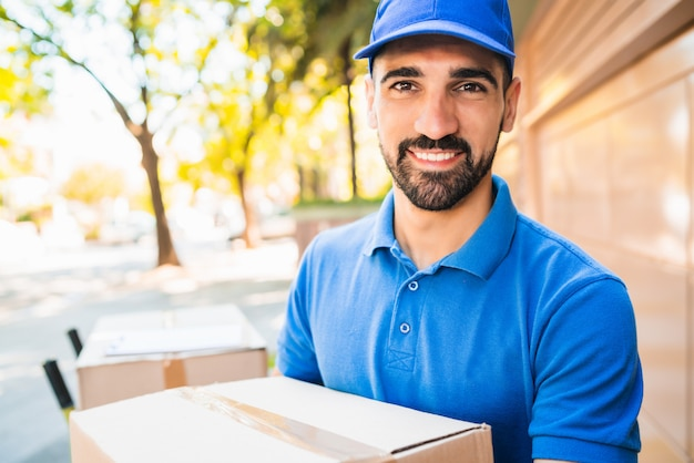 Delivery man carrying package outdoors.