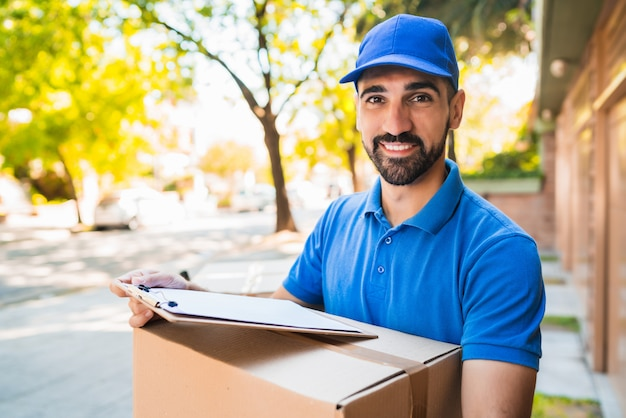 Delivery man carrying package outdoors