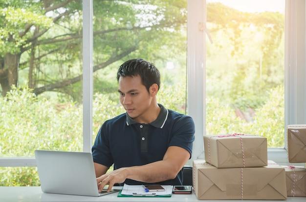 Доставка человек, проверяющий адрес, чтобы отправить картонную коробку с ноутбуком