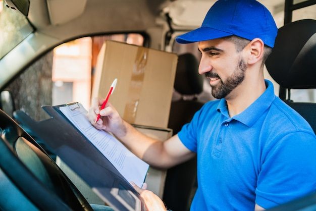 Delivery man checking delivery list in van