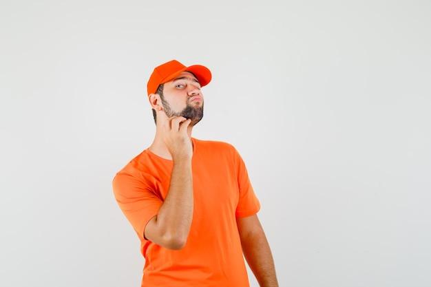 Uomo di consegna che controlla la pelle del viso toccando la barba in maglietta arancione, berretto e guardando elegante, vista frontale.