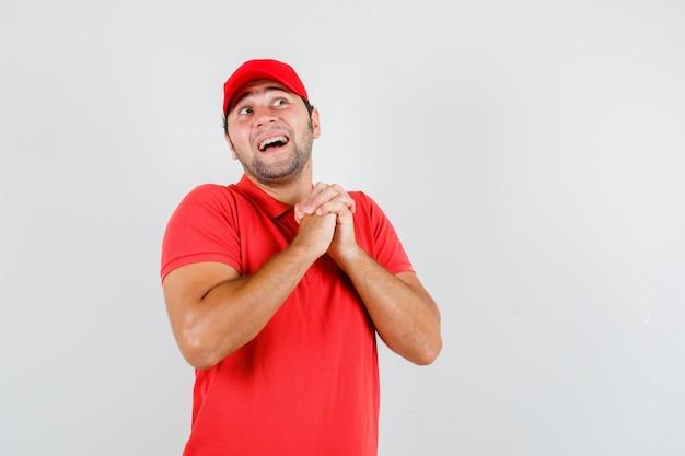赤いtシャツの祈りのジェスチャーで手を握り締める配達人