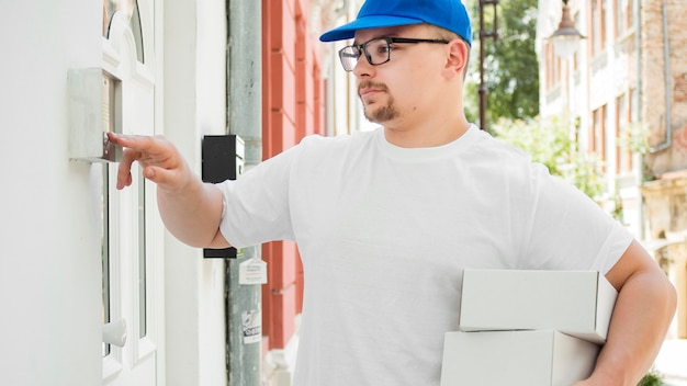 Delivery man clicking on bell medium shot