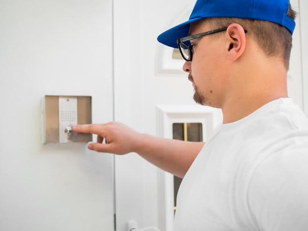 Delivery man clicking on bell side view