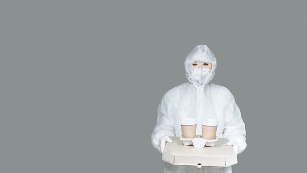Delivery man courier girl in a protective suit, gloves, mask on a gray