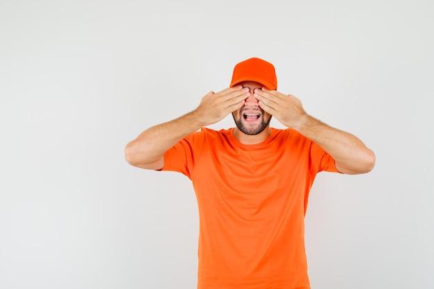 Uomo di consegna che copre gli occhi con le mani in maglietta arancione, berretto e sembra eccitato. vista frontale.
