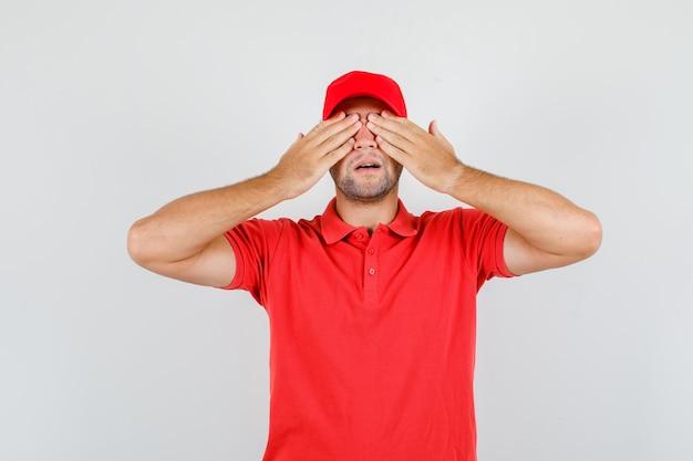 Uomo di consegna che copre gli occhi con le mani in maglietta rossa