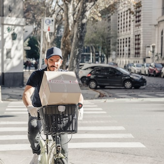 Delivery man crossing street on bicycle with parcel