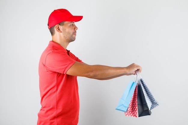 Uomo di consegna che consegna i sacchetti di carta colorati in uniforme rossa