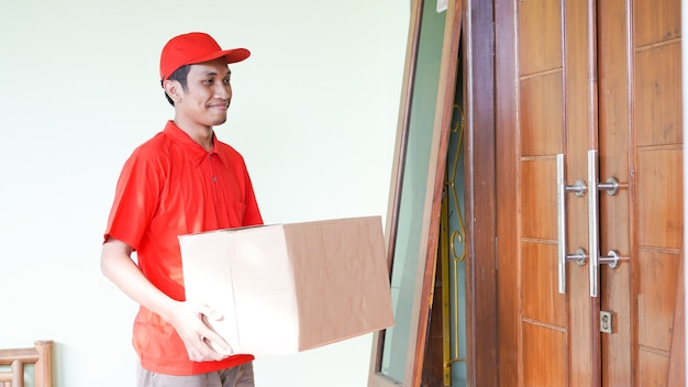 Delivery man delivers the box in front of the customer's house
