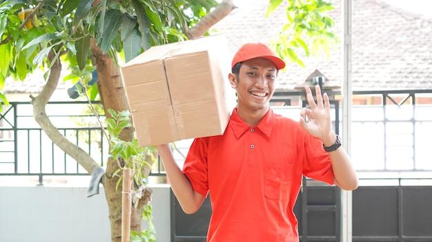 Доставщик доставляет коробку покупателю и жестом ок
