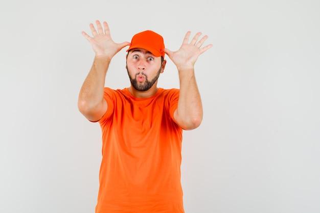 배달원은 주황색 티셔츠를 입은 귀로 손으로 재미있는 제스처를 하고 모자 전면 전망을 보고 있습니다.