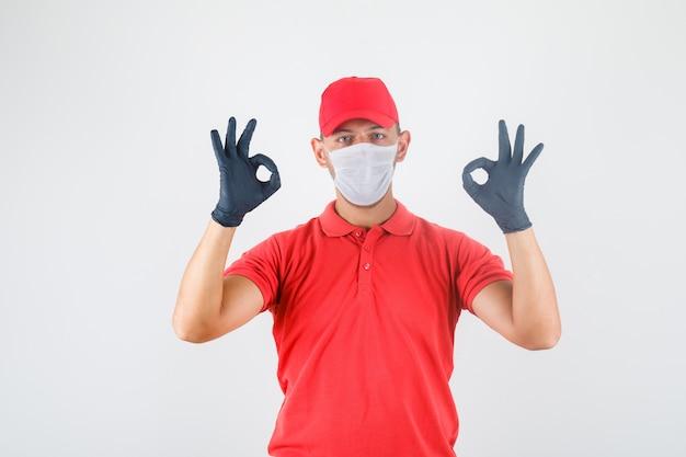 Uomo di consegna che fa segno giusto con le dita in uniforme rossa, mascherina medica, guanti, vista frontale.