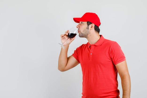 赤いtシャツでアルコールを飲む配達人