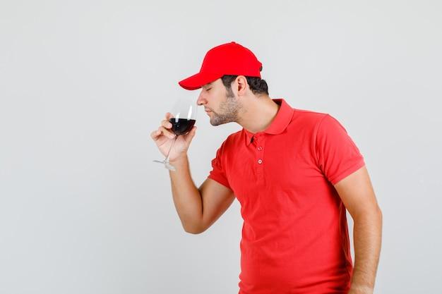Uomo di consegna che beve alcolici in maglietta rossa