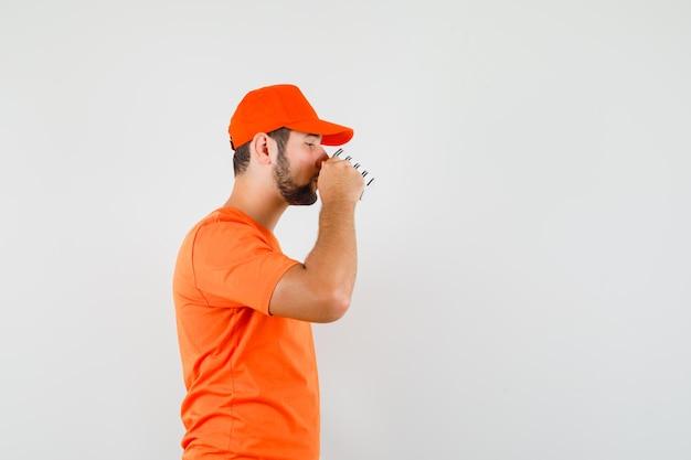오렌지 티셔츠, 모자에 커피를 마시는 배달 남자.