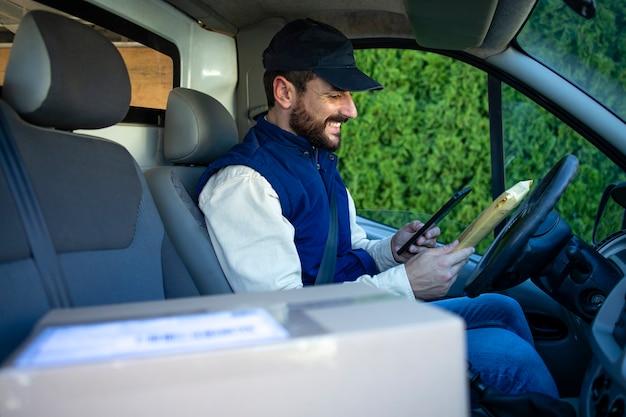 Доставщик за рулем своего фургона с пакетами на переднем сиденье.