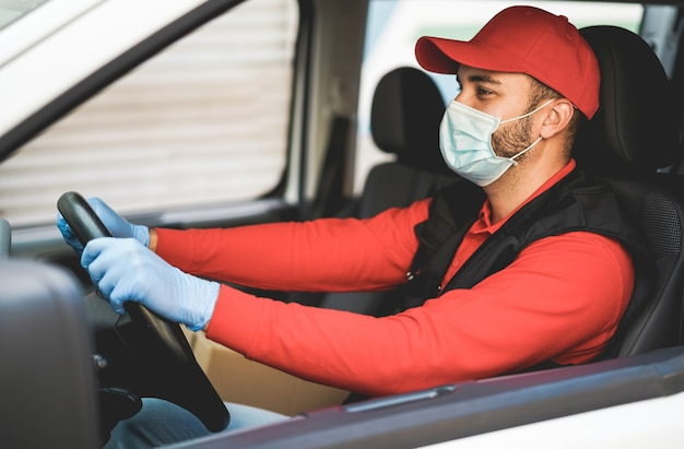 Delivery man driving a van during coronavirus outbreak - focus on hat