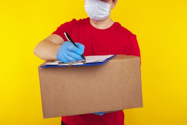 フェイスマスク手袋の配達人従業員は黄色で隔離の空の段ボール箱を保持します