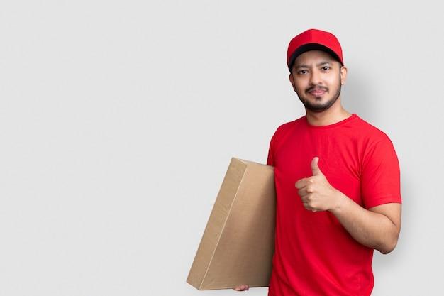 赤い帽子の空白のtシャツの指の制服の配達人従業員は、白い背景で隔離の空の段ボール箱を保持します。