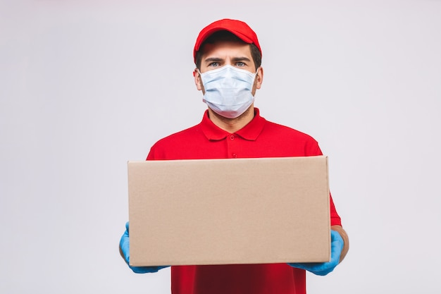 Работник работника доставляющего покупки на дом в перчатках маски стороны футболки пробела красной крышки равномерных держит пустую картонную коробку изолированный на белой стене. служба карантинной пандемической коронавирусной вирусной концепции 2019-нков.