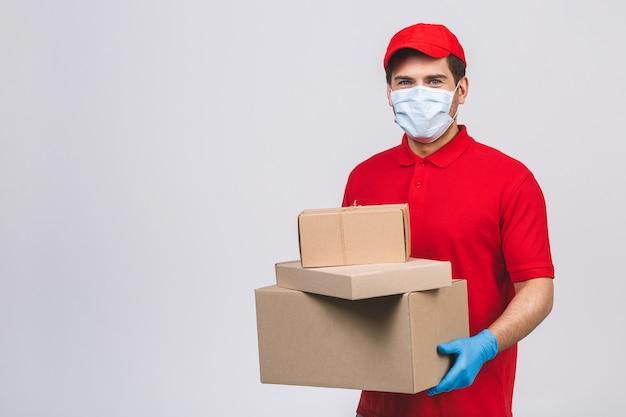 빨간 모자 빈 티셔츠 유니폼 얼굴 마스크 장갑에 배달 남자 직원은 빈 골판지 상자를 개최