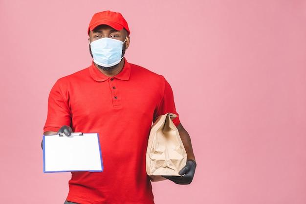 赤い帽子の空白のtシャツの制服のフェイスマスクの手袋で配達人の従業員は空の段ボール箱を保持します