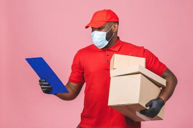 Сотрудник доставляющего покупки на дом в красной кепке пустая футболка, равномерные перчатки с маской для лица, держит пустую картонную коробку.