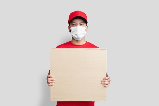 赤い帽子の空白のtシャツの制服のフェイスマスクの配達人従業員は、白い背景で隔離の空の段ボール箱を保持します。