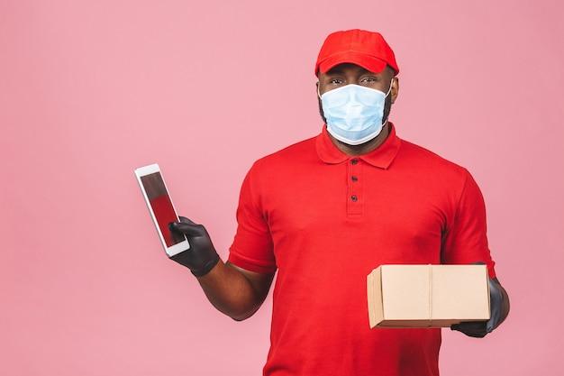 赤いキャップの空白のtシャツの制服のフェイスマスクの手袋で配達人の従業員は空の段ボール箱を保持します