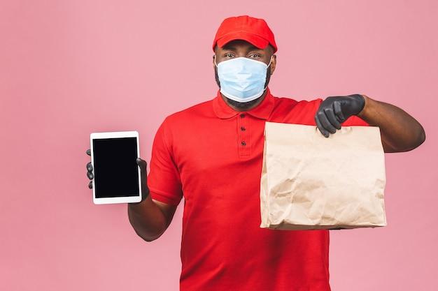 Сотрудник курьера в красной кепке, пустая футболка, униформа, маска для лица, перчатка, держит пустую картонную коробку