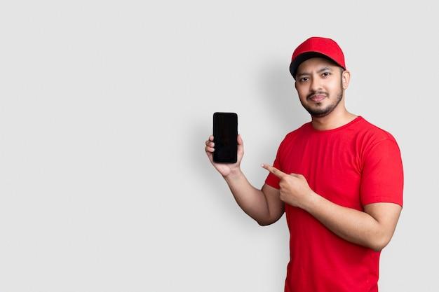 赤い帽子の空白のtシャツの制服を着た配達人の従業員は、白い背景で隔離の黒い携帯電話アプリケーションを保持します。