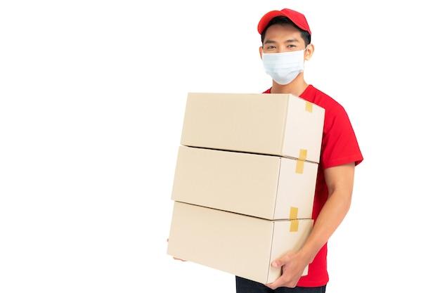 白い背景で隔離空の段ボール箱を保持している赤いtシャツ制服フェイスマスクの配達人従業員