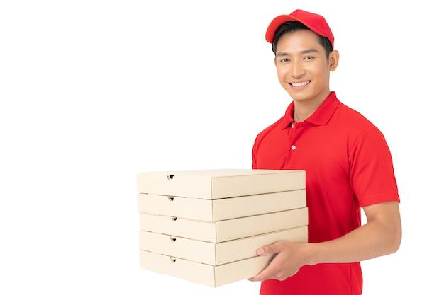 白い背景で隔離空の段ボール箱を保持している赤いtシャツの制服を着た配達人従業員