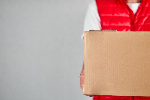 赤いベストの制服を着た配達員の従業員は、分離された空の段ボール箱を保持します
