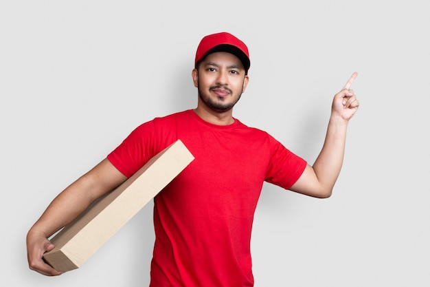Delivery man employee in red cap blank t-shirt finger uniform hold empty cardboard box isolated on white