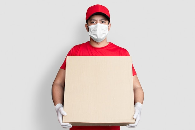 Delivery man employee in red cap blank t-shirt uniform face mask hold empty cardboard box isolated on white background