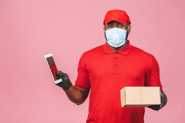 Delivery man employee in red cap blank tshirt uniform face mask glove hold empty cardboard box