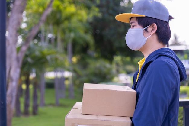 Работник доставляющий покупки на дом нося лицевую маску и держа коробки снаружи.