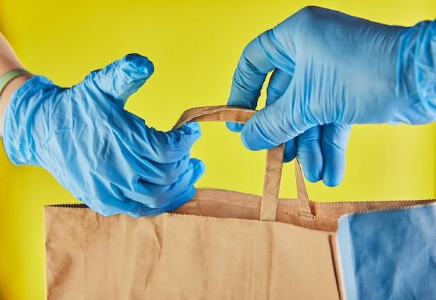 Работодатель работника доставляющего покупки на дом в голубых перчатках держит сумку ремесла бумажную при еда, изолированная на желтой студии. служба карантинной пандемической коронавирусной вирусной концепции 2019-нков.