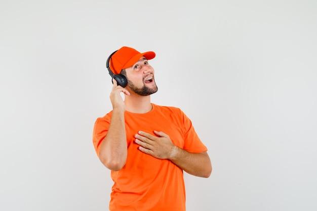 주황색 티셔츠, 모자를 쓴 헤드폰으로 음악을 즐기고 앞모습을 바라보는 행복한 배달원.