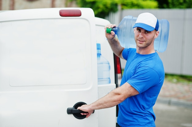 Delivery man in front of cargo van delivering bottles of water