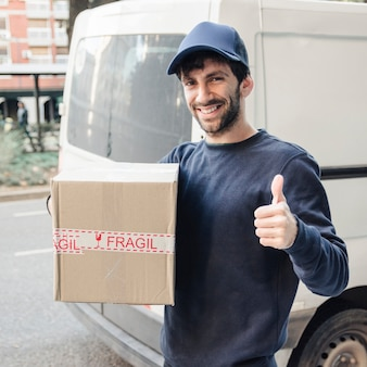 Delivery man gesturing thumbs up while holding parcel