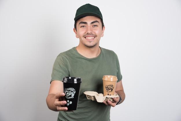 Uomo di consegna regalando caffè su sfondo bianco.