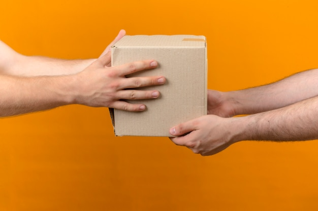 Uomo di consegna che dà il pacchetto della scatola al cliente sulla vista laterale arancione isolata